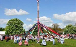 In England, a large Maypole is placed on a village green and people dance around it to celebrate the coming summer.