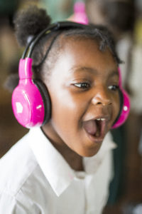 A girl wearing now>press>play pink wireless headphones