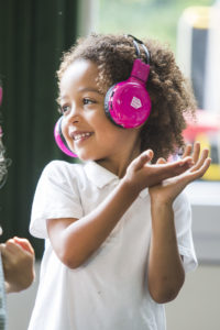 A child wearing now>press>play headphones.