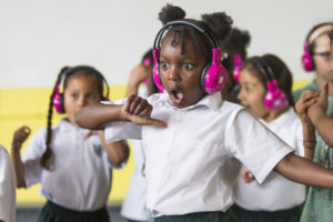 Children wearing now>press>play pink wireless headphones pull a 'wow' face