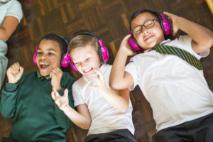 Children wearing now>press>play headphones lie on the floor during an experience.