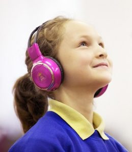 A girl wearing now>press>play headphones.