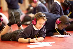 Children wearing now>press>play headphones lie on the floor completing a worksheet during an experience.