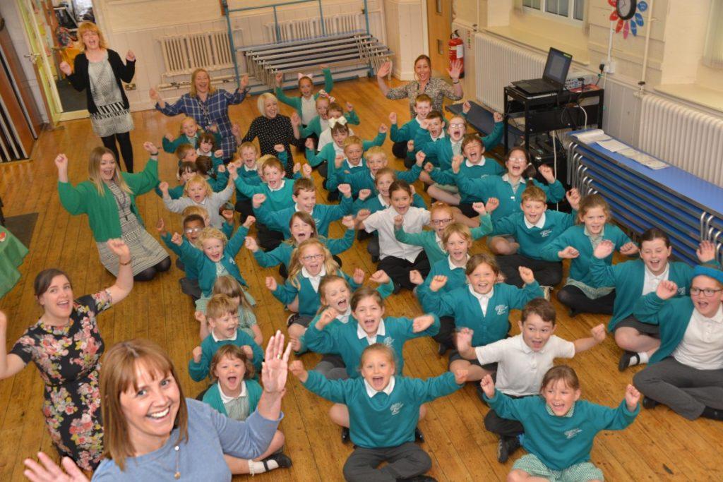 Children and teachers cheering