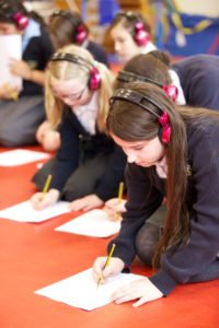 Children wearing now press play headphones kneel on the floor completing worksheets during an experience.