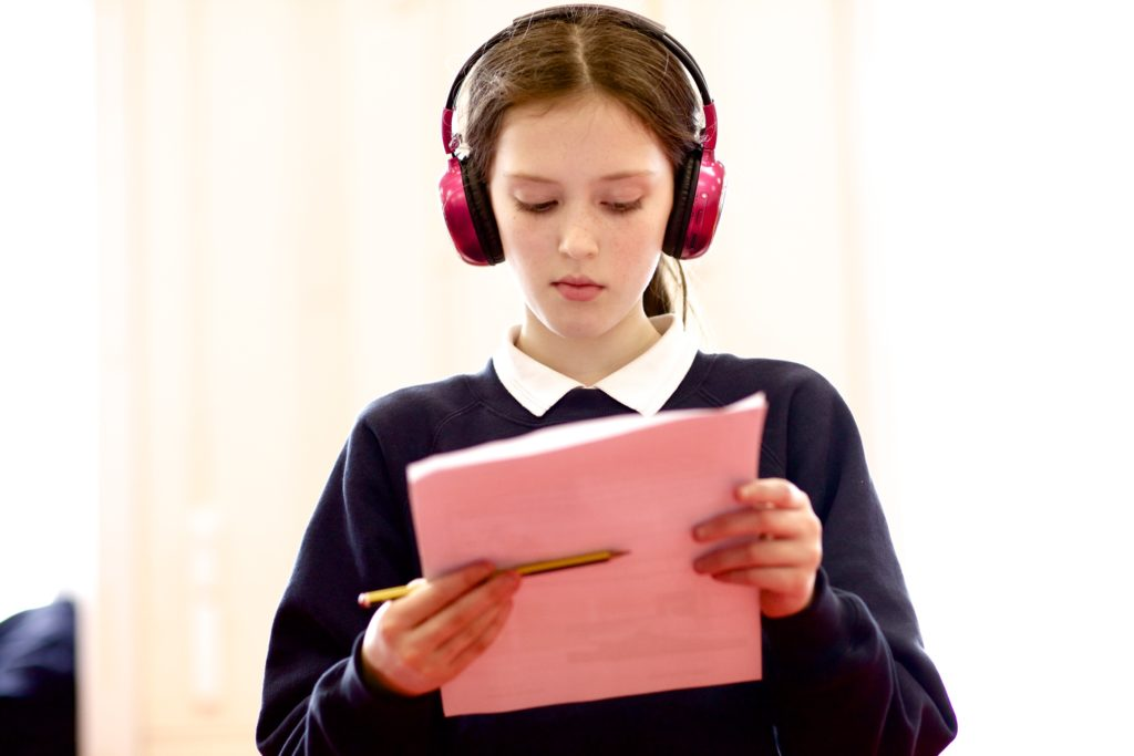 A girl wearing now press play headphones completes a worksheet during an experience.