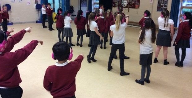 Children standing wearing now press play headphones enact a scene during an experience.