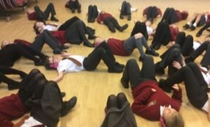 Children lying down wearing now press play headphones enact a scene during an experience.