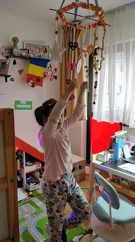 Student with her arms in the air while doing an audio experience at home
