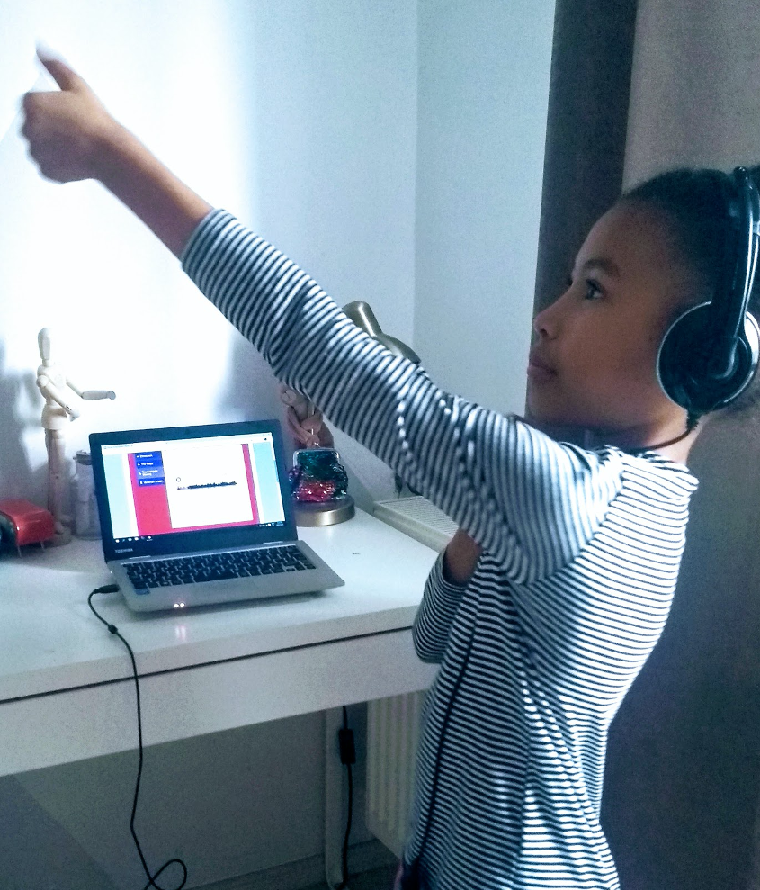 Student doing a now>press>play audio experience at home, pointing at the ceiling