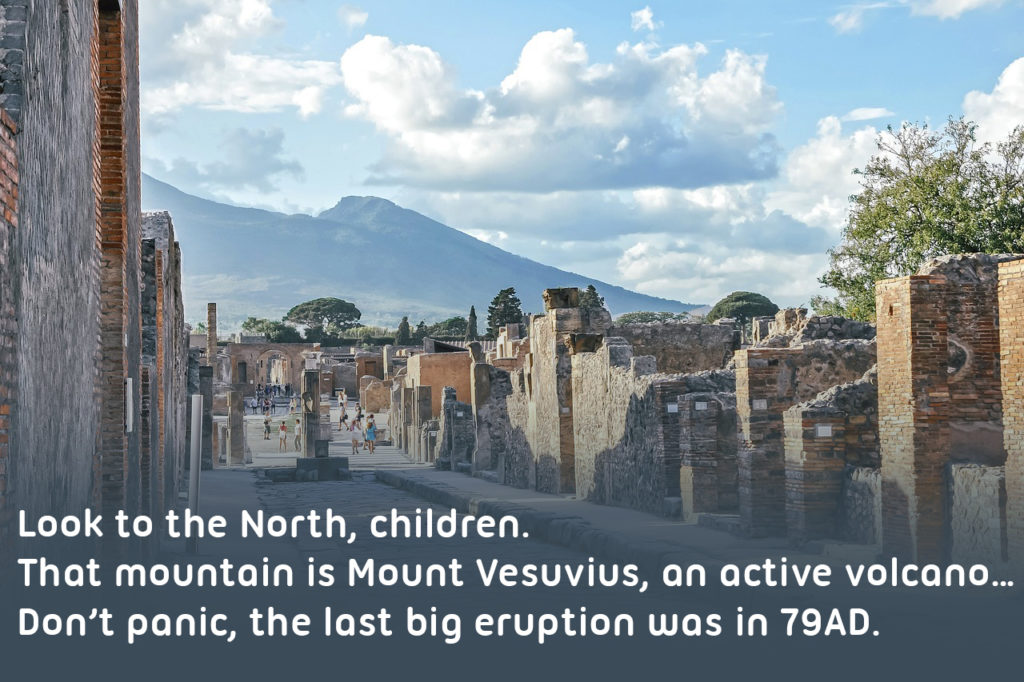 Image of pompeii with text reading: Look to the North, children. That mountain is Mount Vesuvius, an active volcano… Don't panic, the last big eruption was in 79AD.